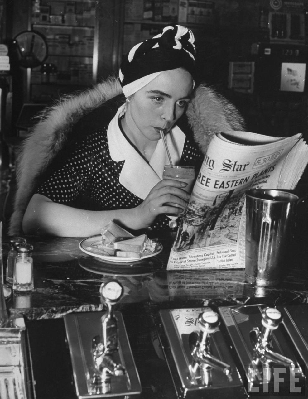 WomanReadingNewspaperDrinkingChocolateShakeWearingTurban1940
